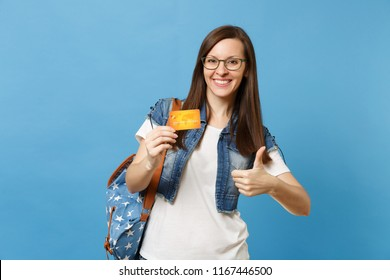 Portrait of young joyful pleasant woman student in denim clothes, glasses with backpack showing thumb up holding credit card isolated on blue background. Education in high school university college