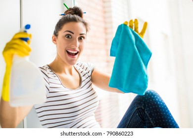 Portrait of the young joyful woman who sitting near the window in the room and holding rag and window cleaner in hands in gloves