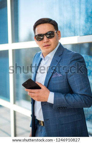 ee41da4e8f Portrait of a young kazakh man professional banker working on mobile phone  while standing in modern office outdoors. Portrait of asian handsome  businessman ...