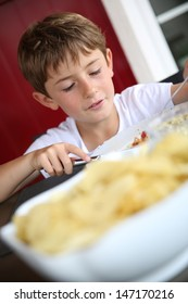 Portrait of young kid eating grilled food in summer