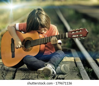 Portrait of young kid playing guitar