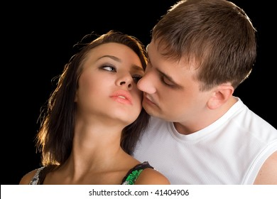 Portrait of young kissing couple. Isolated on black