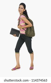 Portrait of a young lady carrying a bag and books