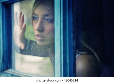Portrait of the young lady indoors looking through the window