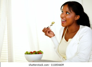 Portrait of a young lady looking to her right while eating a vegetarian salad on a light background. With copyspace.