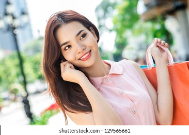 Portrait of a young lady with shopping bags and mobile phones in hands