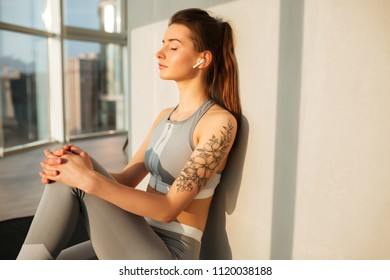 Portrait of young lady in sporty top and leggings sitting on yoga mat and listening music in earphones while dreamily closing her eyes at home with big beautiful windows isolated