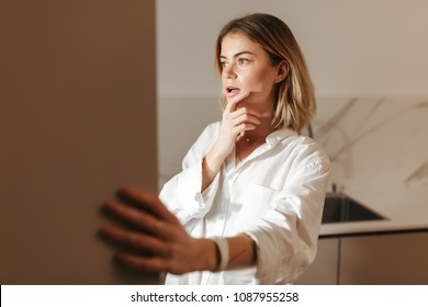 Portrait of young lady standing on kitchen at night and thoughtfully looking in open fridge at home isolated