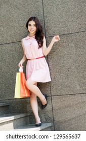 Portrait of a young lady standing with shopping bags near the wall