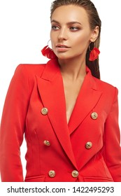 Portrait of young lady with tied back hair, wearing red blazer and dangle earrings with beaded rich red tassels in view of waver. The girl with plush lips is looking to side against snowy background.