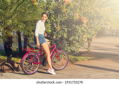 A portrait of young latin girl riding a bicycle in a city park smiling on a sunny day