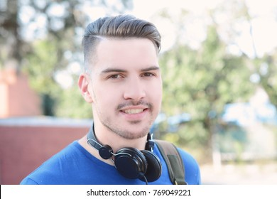 Portrait of young latin man listening to music with headphones. Outdoors.