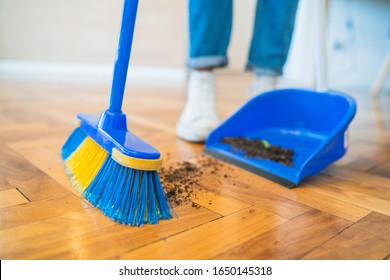 Portrait of young latin man sweeping wooden floor with broom at home. Cleaning, housework and housekeeping concept.