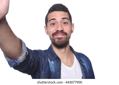 Portrait of young latin man taking selfie. Isolated white background.