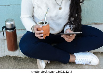 Portrait of Young latin woman drinking traditional Argentinian yerba mate tea with tablet. South american popular drink. Outdoors