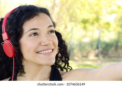 Portrait of young latin woman with headphones listening to music at the park in summer. Enjoying Music.