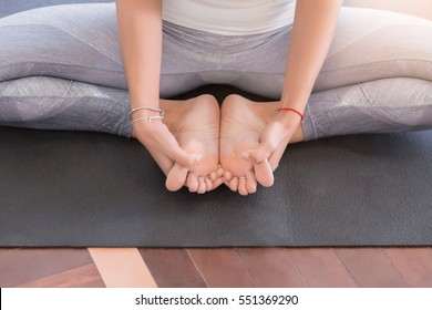 Portrait of young latin woman working out, doing butterfly yoga pose. Yoga exercise, sitting in cobbler pose, close up feet