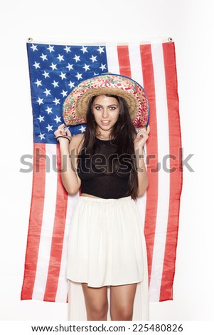 8dcb8785b820 Portrait of a young Latina girl in sombrero on the background of the American  flag. Portrait of woman on white background
