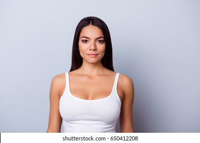 Portrait of a young latino american mulatto girl. She is in a casual white singlet standing on the pure light blue background