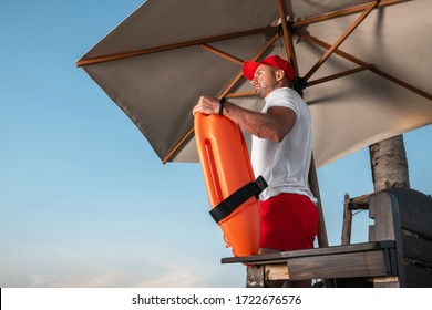 Portrait of a young lifeguard with a rescue orange buoy. Security measures on the beach.