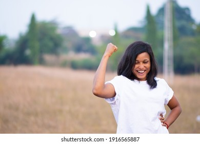 portrait of a young light skin nigerian woman flexing her muscle to express strength