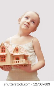 portrait of young little girl holding scale house model showing dreaming facial expression. isolated