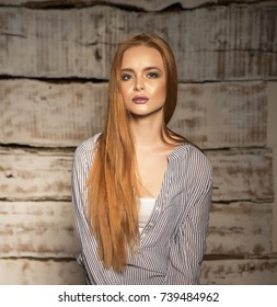Portrait of a young long-haired ginger girl, close up studio shot