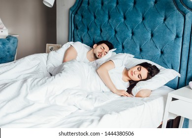 Portrait of young lovely couple sleeping in the bed on white blankets  to each other. Healthy lifestyle. Relationships , closeness. Healthy lifestyle. Wellness concept