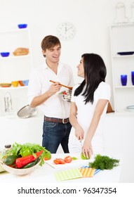 portrait of young lovely couple slicing tomato in their kitchen, happy smile looking to each other