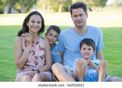 Portrait young lovely happy family with sons sitting relaxed smiling in park outdoors, blurred background.