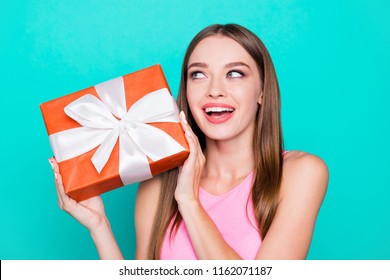 Portrait of young lovely nice sweet glamorous girl lady, wearing pink top, carrying gift box, wondering about surprise. Isolated over bright vivid teal turquoise background