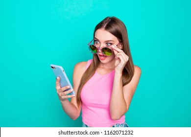 Portrait of young lovely nice sweet girl lady wearing sun glasses, excited, reading sms in phone. Isolated over bright vivid teal turquoise background