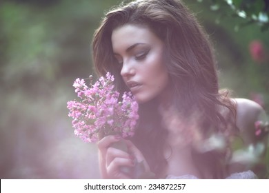 Portrait of young lovely woman in spring flowers. Beauty Romantic Girl Outdoors.  Blowing Long Hair. Glow  Backlit.