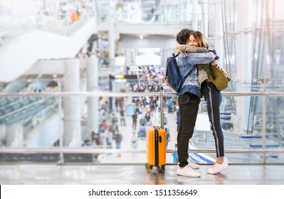 Portrait of young loving couple hug in airport terminal. Young happy traveler man and woman with copy space. Tourist people lifestyle happy honeymoon concept.
