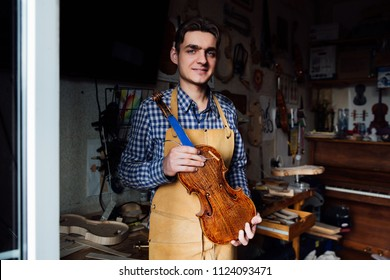 portrait of a young luthier with a handcrafted violin in his workshop with the tools and the woods on the background. Master artist poses in his home workshop. Holds violin-workpiece.