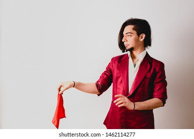 Portrait of young magician handling ropes and bandanas to do magic tricks, isolated on white.