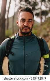 Portrait of young male athlete standing outdoors and looking at camera. Male runner outdoors on country road.