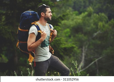 Portrait of young male backpacker with a rucksack standing on the mountain hill while enjoying nature scenery view with plants copy space area background for your text message or advertising content