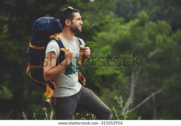 Porträt von jungen männlichen Rucksacktouristen mit Rucksack auf dem Berghang, während Sie die Naturlandschaft mit Pflanzen genießen Kopienraum-Hintergrund für Ihre Textnachricht oder Werbeinhalte