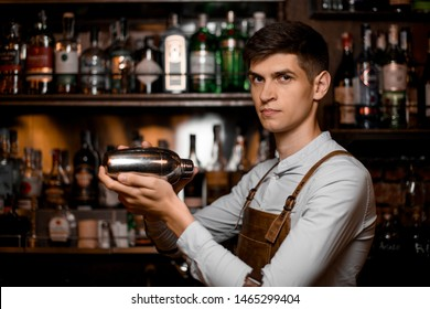 Portrait of young male bartender in leather apron with steel shaker