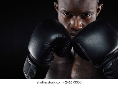 Portrait of a young male boxer in a fighting stance on black background. Young man doing boxing exercise.