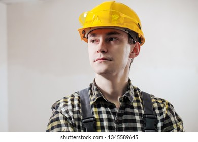 Portrait of a young male builder and repairman in a yellow helmet against the background of a wall. The concept of construction.