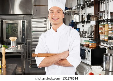 Portrait of young male chef holding pin roll in commercial kitchen