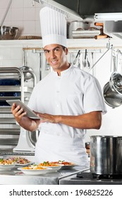 Portrait of young male chef holding digital tablet with pasta dishes at commercial kitchen counter