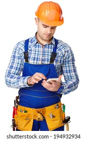 Portrait of young male construction worker with smart-phone wearing protective clothes, helmet and tool belt isolated on white background