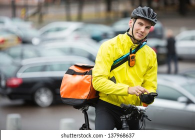 Portrait of young male cyclist with courier delivery bag using mobile phone on street