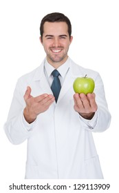 Portrait Of Young Male Doctor Holding Green Apple. Isolated On White
