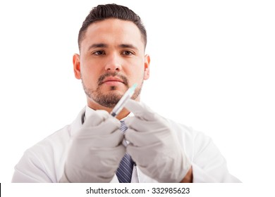 Portrait of a young male doctor wearing gloves and preparing a syringe for a patient