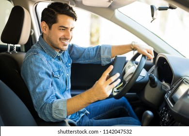 Portrait of young male driver using his mobile phone while driving the car and smiling