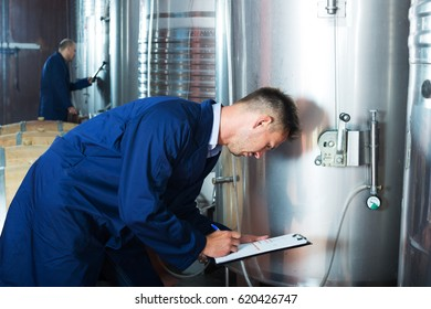 portrait of young male expert wearing coat standing and taking off data from equipment in winery